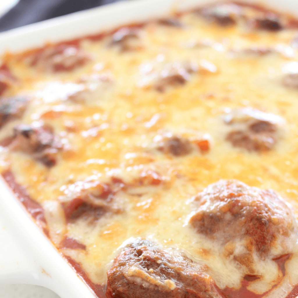 These cheesy baked meatballs are one of those easy dinners that the entire family is sure to love.  The beef meatballs are baked in a tomato sauce, and topped with plenty of cheese.